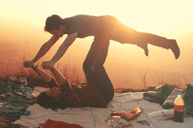 woman-lying-on-blanket-under-man-on-her-legs-holding-hands